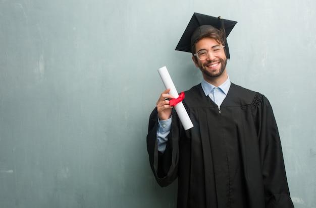 Giovane uomo laureato contro una parete del grunge con uno spazio di copia allegro e con un grande sorriso