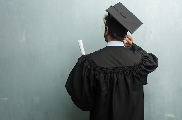 Giovane uomo laureato contro una parete di grunge con uno spazio di copia mostrando indietro, in posa e in attesa, guardando indietro