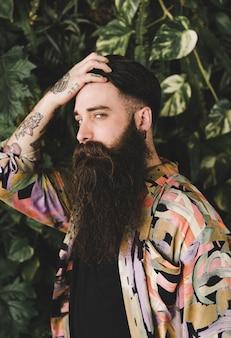 Giovane uomo lungo barbuto con le mani sulla testa che guarda l'obbiettivo