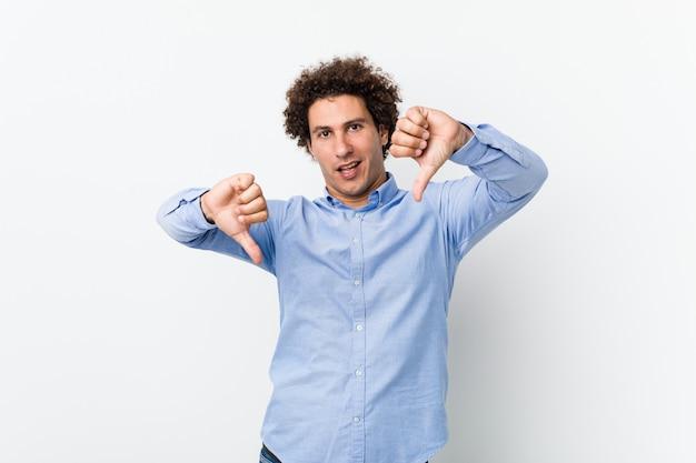 Giovane uomo maturo riccio che indossa una camicia elegante che mostra il pollice verso il basso e che esprime antipatia.