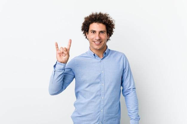 Giovane uomo maturo riccio che indossa una camicia elegante che mostra un gesto di corna