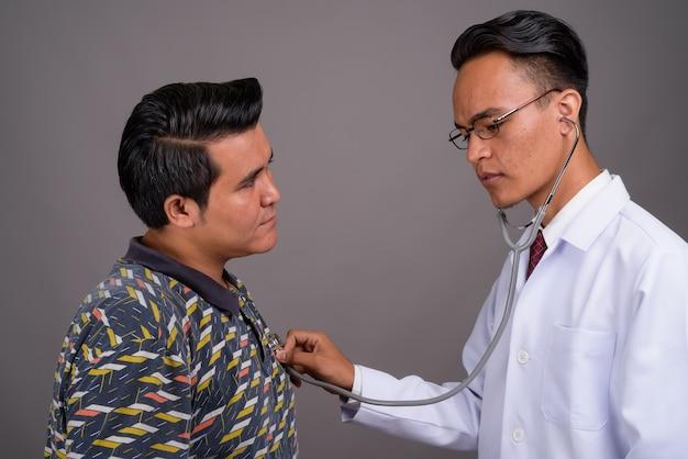 Giovane uomo multietnico e giovane medico indiano contro la parete grigia