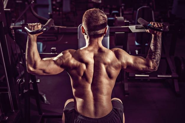 Giovane uomo muscolare che fa esercizio duro con le teste di legno per i delta medi delle spalle in macchina di addestramento alla palestra