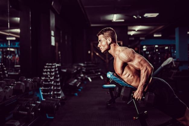 Giovane uomo muscolare che fa esercizio duro con le teste di legno per i delta posteriori delle spalle sul banco di addestramento alla palestra