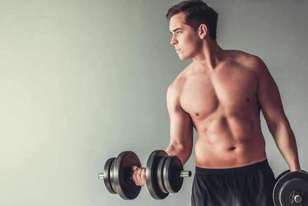 Giovane uomo muscolare che fa le esercitazioni con i dumbbells.