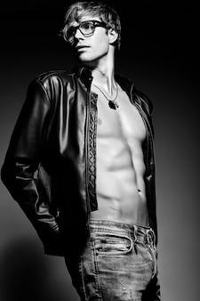 Giovane uomo muscoloso in forma muscoloso bello modello in posa in studio che mostra i suoi muscoli addominali in giacca di pelle