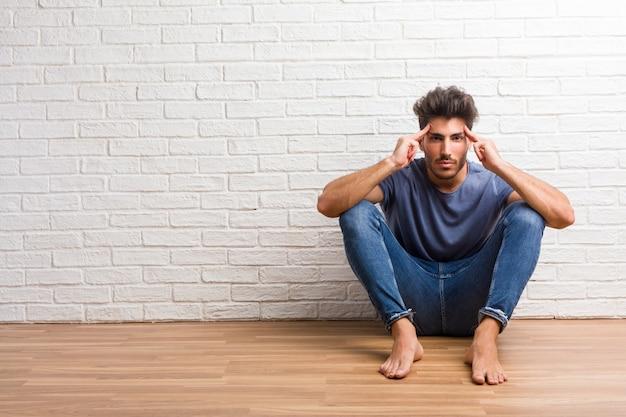 Giovane uomo naturale sedersi su un pavimento in legno uomo facendo un gesto di concentrazione