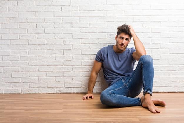Giovane uomo naturale seduto su un pavimento di legno preoccupato e sopraffatto, smemorato, realizza qualcosa