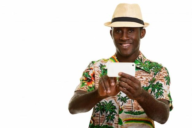 Giovane uomo nero africano felice che sorride e che prende immagine con il cellulare