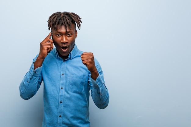 Giovane uomo nero di rasta che tiene un telefono che incoraggia spensierato ed eccitato. concetto di vittoria