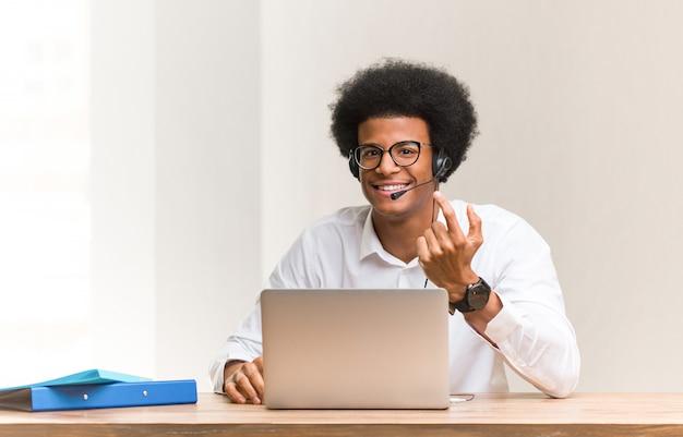 Giovane uomo nero telemarketer che invita a venire