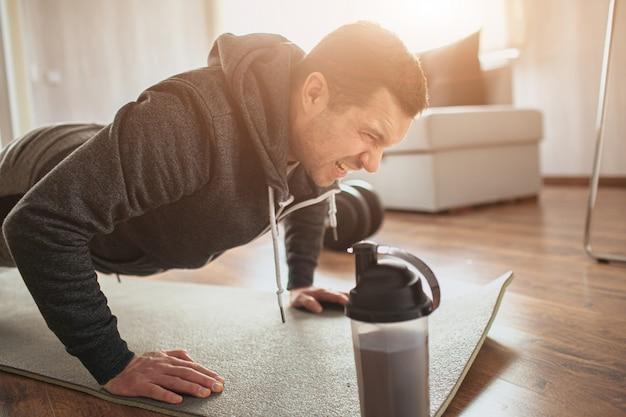 Giovane uomo ordinario che fa sport a casa. plancia in posizione sui pugni o facendo flessioni.