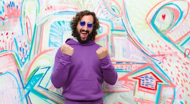 Giovane uomo pazzo barbuto che grida trionfalmente, ridendo e sentendosi felice ed eccitato mentre celebra il successo contro il muro di graffiti