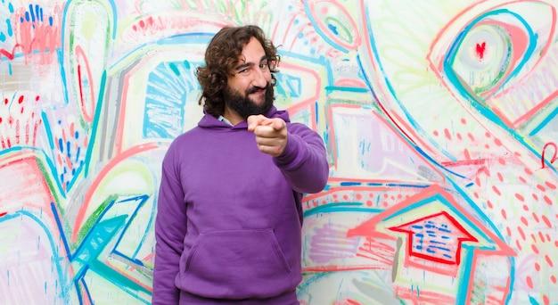 Giovane uomo pazzo barbuto che punta alla fotocamera con un sorriso soddisfatto, fiducioso, amichevole, scegliendovi sulla parete dei graffiti