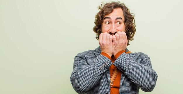 Giovane uomo pazzo barbuto che sembra preoccupato, ansioso, stressato e impaurito, mordendosi le unghie e guardando allo spazio laterale della copia contro la parete di colore piatto