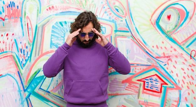 Giovane uomo pazzo barbuto che sembra stressato e frustrato, che lavora sotto pressione con un mal di testa e turbato da problemi sulla parete dei graffiti