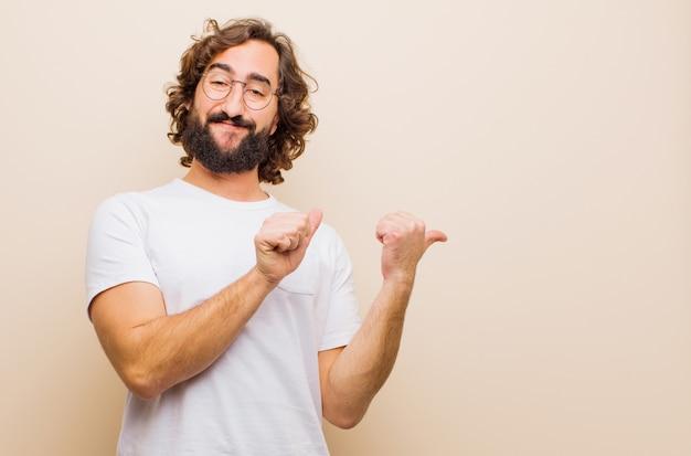 Giovane uomo pazzo barbuto che sorride allegramente e con indifferenza indicando lo spazio laterale, sentendosi felice e soddisfatto contro la parete di colore piatto