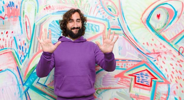 Giovane uomo pazzo barbuto che sorride e che sembra amichevole, mostrando numero dieci o decimo con la mano in avanti, conto alla rovescia contro la parete dei graffiti