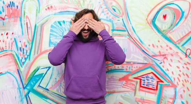 Giovane uomo pazzo barbuto che sorride e che si sente felice, coprendo gli occhi con entrambe le mani e aspettando un'incredibile sorpresa contro il muro di graffiti
