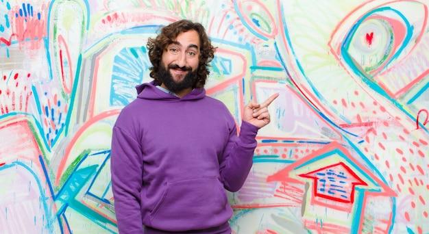 Giovane uomo pazzo barbuto che sorride felicemente e guarda lateralmente, chiedendosi, pensando o avendo un'idea contro il muro di graffiti