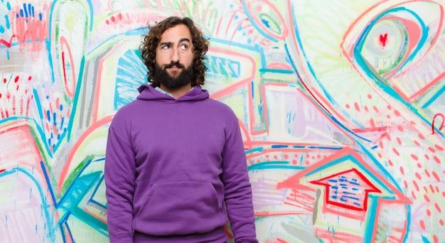 Giovane uomo pazzo barbuto con un'espressione preoccupata, confusa, all'oscuro, alzando lo sguardo a copyspace, dubitando contro i graffiti