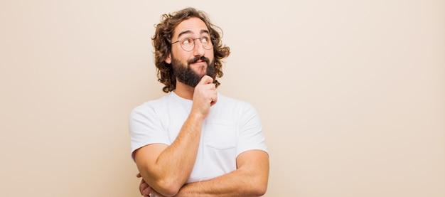 Giovane uomo pazzo barbuto sentirsi pensieroso, chiedersi o immaginare idee, sognare ad occhi aperti e alzare lo sguardo per copiare lo spazio contro il muro rosa
