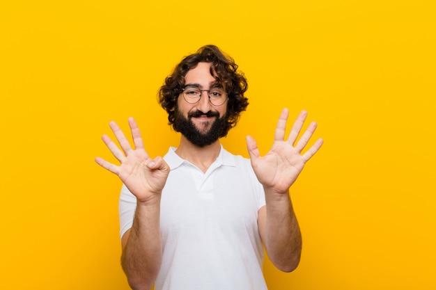 Giovane uomo pazzo che sorride e che sembra mostrando numero nove o nono amichevole con il conto alla rovescia di andata della mano