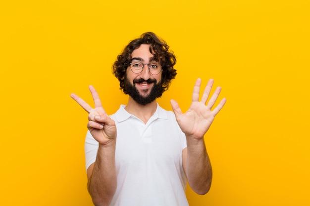 Giovane uomo pazzo che sorride e che sembra mostrando numero sette o settimo amichevole con il conto alla rovescia di andata della mano