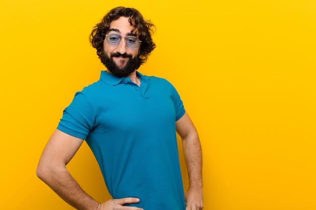 Giovane uomo pazzo che sorride felicemente con una mano sull'anca e sulla parete arancio attitudine sicura, positiva, fiera e amichevole