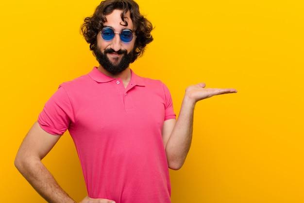 Giovane uomo pazzo che sorride, sentendosi sicuro, riuscito e felice, mostrando l'idea su copyspace sulla parete arancio laterale