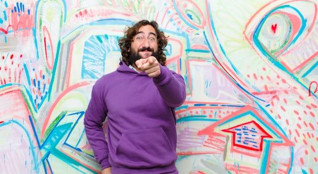Giovane uomo pazzo con la barba che ride di te, indicando la fotocamera e prendendo in giro o deridendoti contro il muro di graffiti