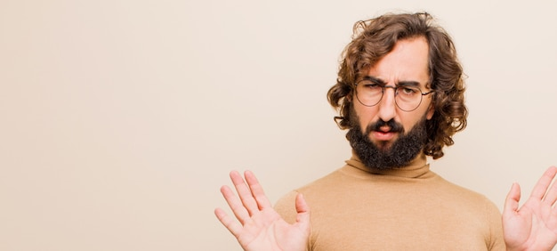 Giovane uomo pazzo con la barba che sembra nervoso, ansioso e preoccupato, dicendo che non è colpa mia o non l'ho fatto contro una parete di colore piatto