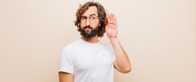 Giovane uomo pazzo con la barba che sembra serio e curioso, ascolta, cerca di ascoltare una conversazione segreta o un pettegolezzo, origliare