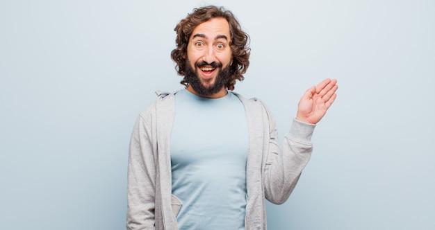 Giovane uomo pazzo con la barba che sorride allegramente e allegramente, agitando la mano, dandoti il benvenuto e salutandoti o dicendo addio contro la parete di colore piatto