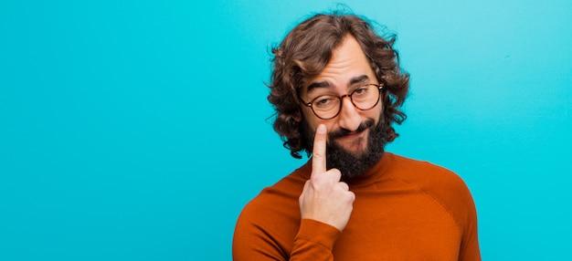 Giovane uomo pazzo con la barba che ti tiene d'occhio, non fidarsi, guardare e stare all'erta e vigile contro la parete di colore piatto