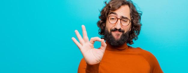 Giovane uomo pazzo con la barba sentirsi felice, rilassato e soddisfatto, mostrando approvazione con gesto ok, sorridendo contro la parete di colore piatto