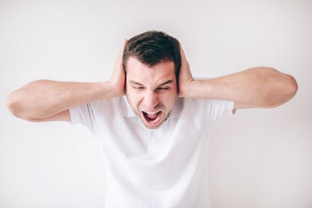 Giovane uomo pazzo isolato sopra la parete bianca. guy urlando, urlando. coprendo le orecchie con le mani. umano pazzo in camicia bianca.
