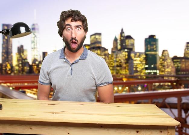 Giovane uomo pazzo su un tavolo sorpreso espressione
