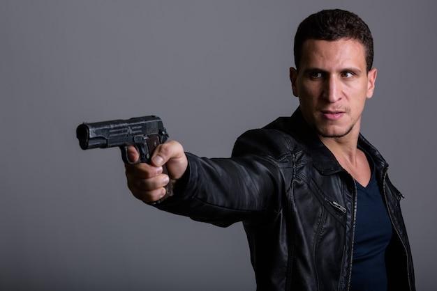 Giovane uomo persiano muscolare arrabbiato che mira a sparare