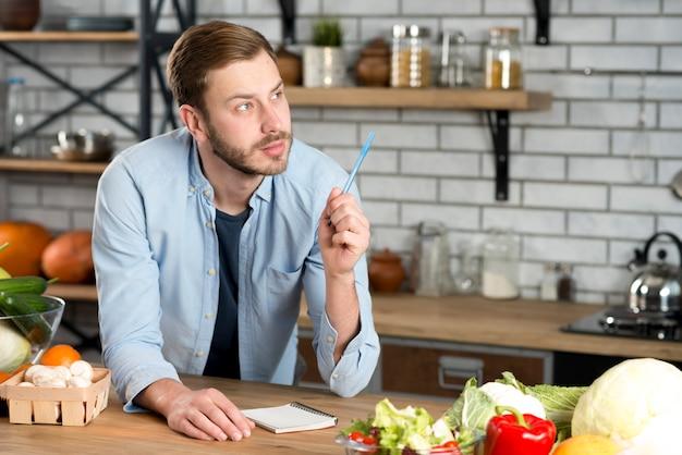 Giovane uomo premuroso, scrivendo la ricetta in cucina con penna e diario