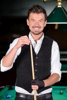 Giovane uomo professionale, giocare a biliardo.