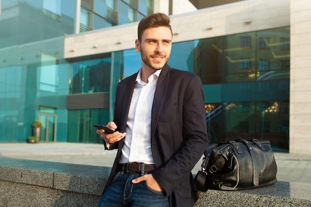 Giovane uomo professionale urbano utilizzando smartphone.