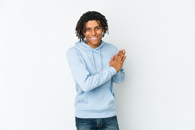 Giovane uomo rasta afroamericano sentirsi energico e confortevole, strofinando le mani fiducioso.