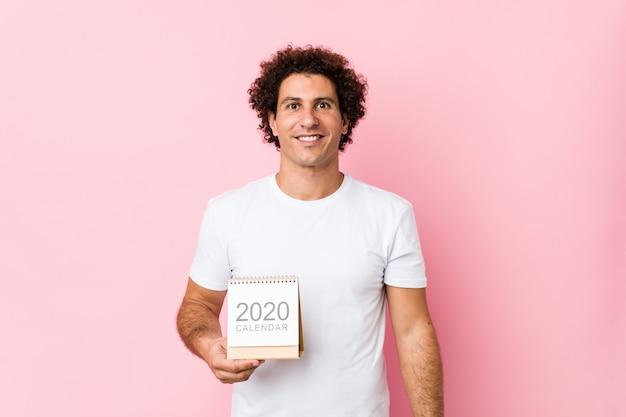 Giovane uomo riccio caucasico che giudica un calendario 2020 felice, sorridente e allegro.