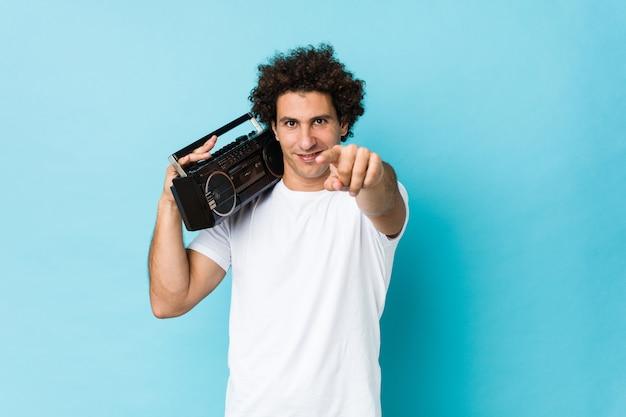 Giovane uomo riccio caucasico che tiene i sorrisi allegri di un guetto blaster che indicano la parte anteriore.