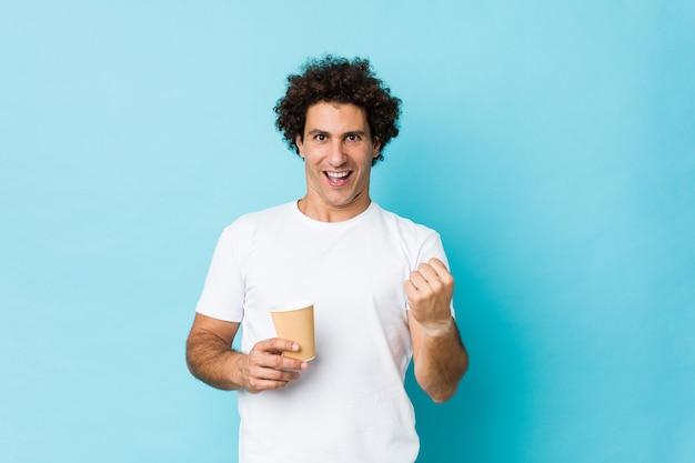 Giovane uomo riccio caucasico che tiene un caffè asportabile che incoraggia spensierato ed eccitato. concetto di vittoria.