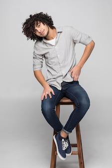 Giovane uomo riccio che si siede su una sedia dello studio isolata sulla parete bianca