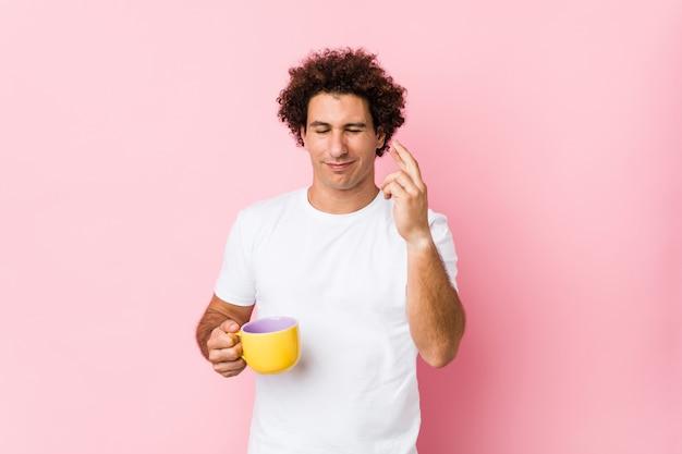 Giovane uomo riccio che tiene le dita dell'incrocio di una tazza di tè per avere fortuna