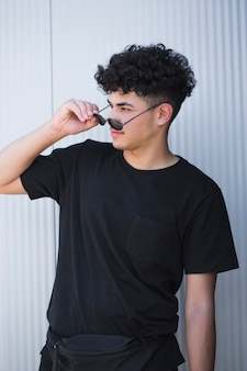Giovane uomo riccio etnico in camicia nera che toglie gli occhiali