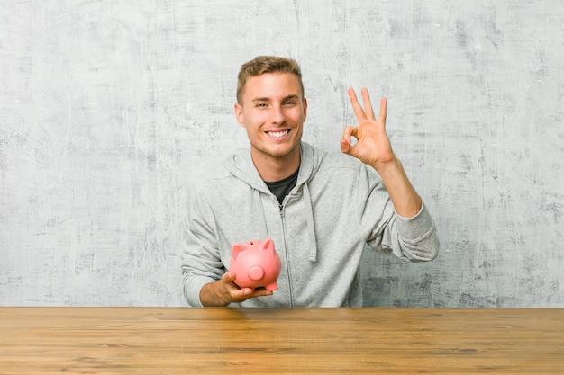 Giovane uomo risparmiando soldi con un salvadanaio allegro e fiducioso mostrando gesto ok.